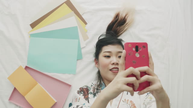 vidéos et rushes de artiste à l'aide de téléphone à côté de papier coloré - une seule femme d'âge moyen