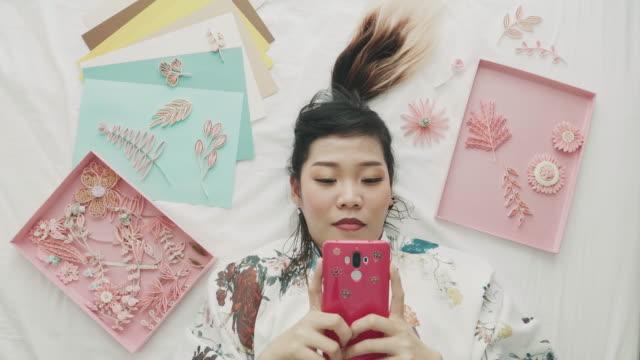 vidéos et rushes de artiste à l'aide de téléphone à côté de son travail - une seule femme d'âge moyen