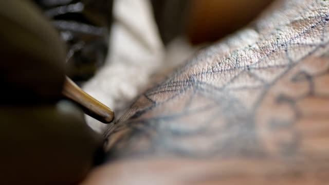 slo mo cu artist using the electric tattoo machine - avambraccio video stock e b–roll