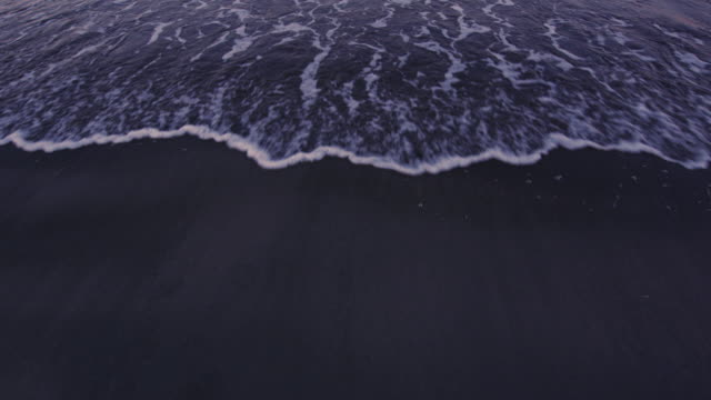 Artistic POV shot of an incoming tide on a sandy beach at sunset. Original stock color video shot in 6K by a RED Dragon camera.
