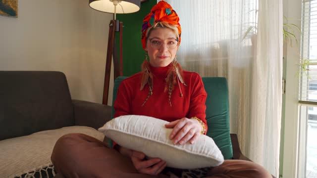 vídeos y material grabado en eventos de stock de joven artística sentada en un acogedor sofá en su sala de estar - distante