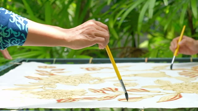artists creating works from candles written on the fabric batik. - batik stock videos and b-roll footage