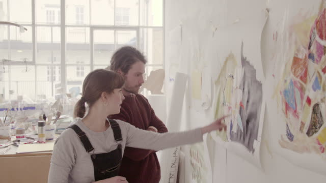 Artists hang abstract painting on wall and discuss painting together.