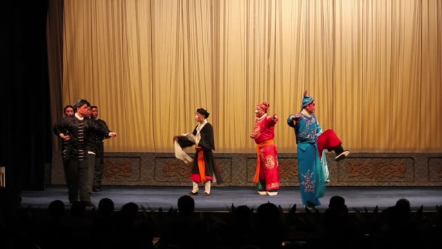 Artists perform a traditional Qinqiang opera on a local stage.