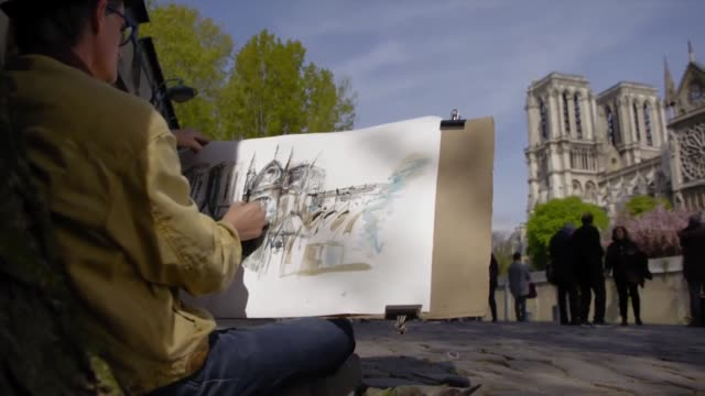 Artists sat along the banks of the Seine drawing the Notre Dame Cathedral after the fire Paris