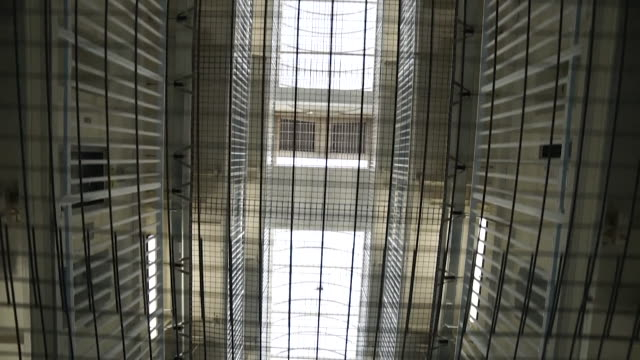arty shot of interiors of hmp liverpool prison showing travelling shot of bars and grates looking upwards towards ceiling - uk prison stock videos & royalty-free footage