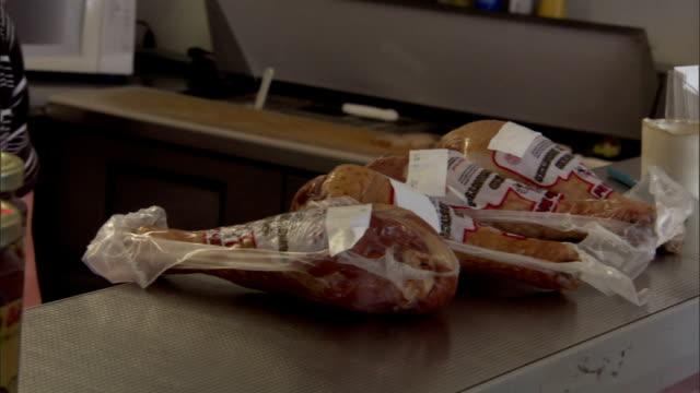 vídeos y material grabado en eventos de stock de as a butcher places wrapped turkey products on a counter, a customer pays cash. - muslo de pollo carne