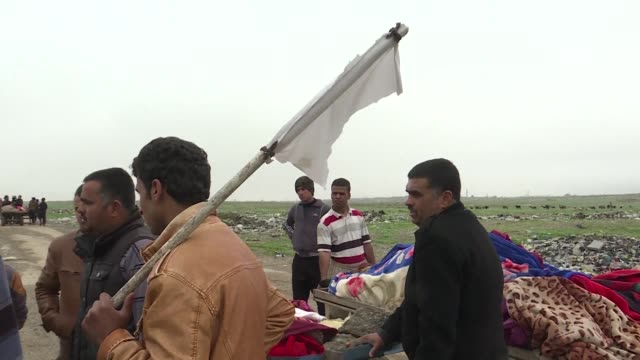 as a convoy of wooden carts descends a hill outside iraq's wartorn second city of mosul a child's foot greyed with dust pokes out from under brightly... - toccare con un dito video stock e b–roll