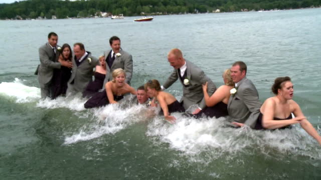 / as a wedding party is taking photographs on a dock the dock collapses and the entire party falls into the lake wedding party blooper on june 23... - ausrutscher stock-videos und b-roll-filmmaterial