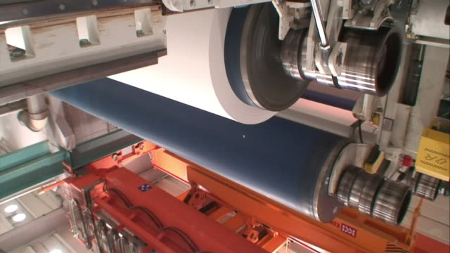 as a wheel spins a blue cylinder raises on a machine in a paper mill. - cylinder stock videos & royalty-free footage