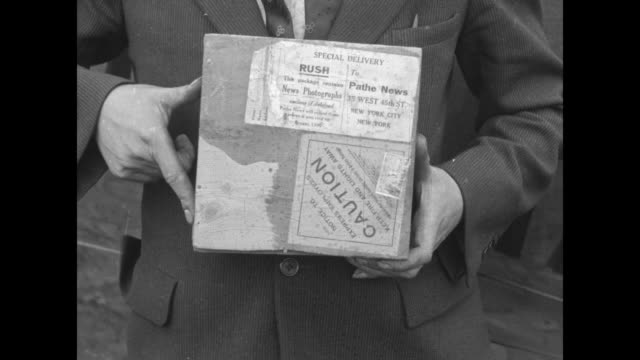 As biplane pilot Lt Wesley Smith looks on a film reel with stamps covering one side is delivered label Special Delivery Rush to Pathe News 35 West...