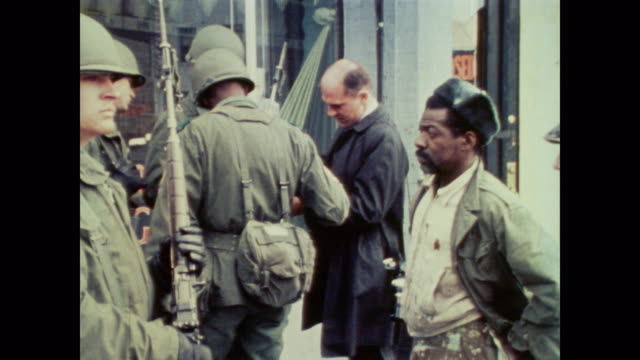 as buildings smolder, national guard soldiers patrol the streets, provide crowd control and talk with the public - 1968 stock videos & royalty-free footage