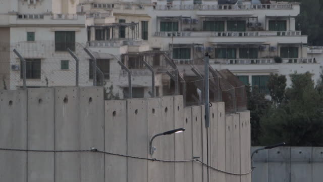 pt 2 as christians flock to bethlehem for christmas a look at life for residents of the divided town shows bethlehem separation barrier and rooftops... - christianity stock videos & royalty-free footage