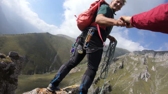 pov as climber approaches summit, reaches to helping hand - top garment stock videos & royalty-free footage