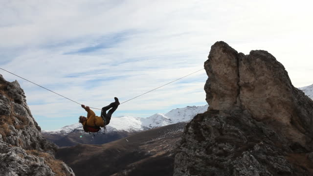 PAN as climber crosses Tyrolean traverse, distant mtns