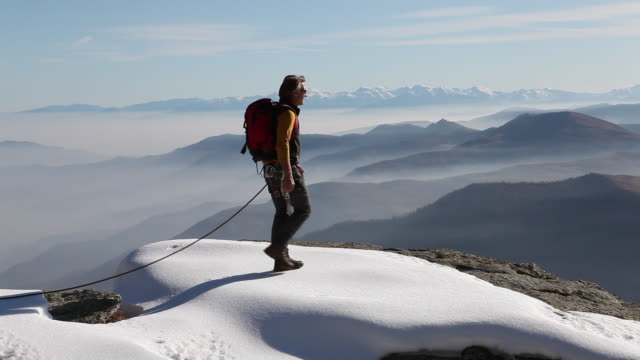 PAN as climber walks to edge of snowy cliff, stretches arms out