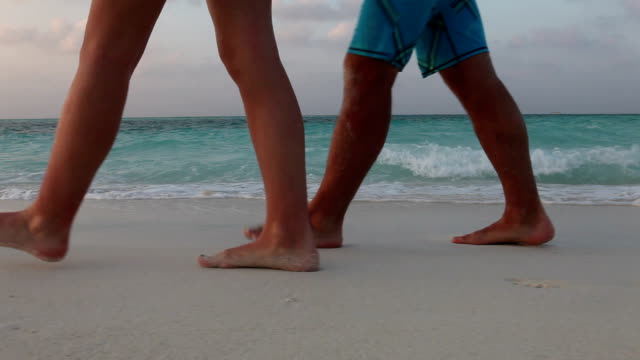 pan as couple walk along white sand beach near water's edge - footprint stock videos and b-roll footage