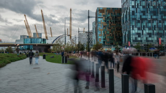 as evening arrives a constant flow of people travel along footpaths towards the o2 entertainment complex a multipurpose indoor arena on the greenwich peninsula in central londo - dome stock videos & royalty-free footage