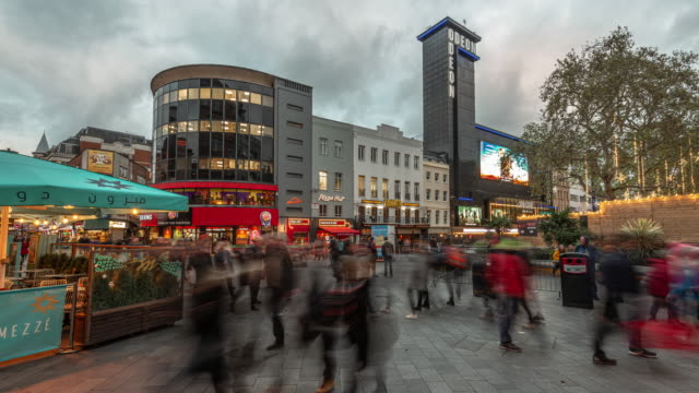 as evening arrives commuters and tourists rapidly move past the iconic cinemas and cafés at leicester square in the west end of london - overcast stock videos & royalty-free footage
