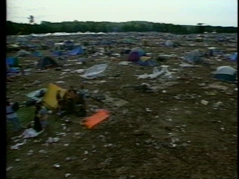 as festival goers walk away, the woodstock '94 music festival field lies covered with litter and tents. - festival goer stock videos & royalty-free footage
