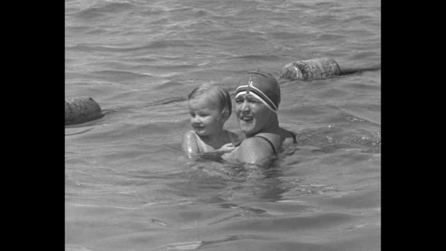 as gertrude ederle gives swimming lessons to children little girl rides on ederle as she is doing backstroke / little girl rides on ederle as she is... - gertrude ederle stock videos & royalty-free footage