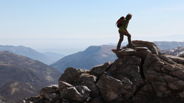 PAN as hiker climbs ridge, jumps in mid-air & pounds fist