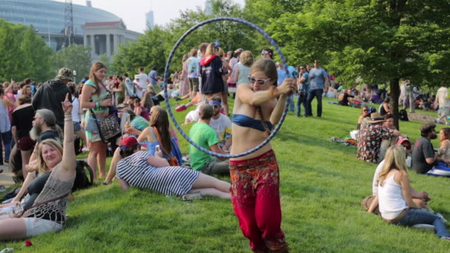 as hundreds of deadheads gather, a woman hula hoops on the grass south of soldier field before the grateful dead concert on the 4th of july. the... - fare video stock e b–roll