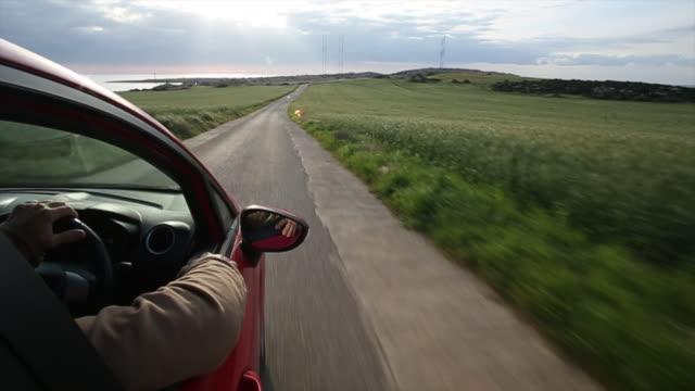 POV as man drives along rural road, past grain fields