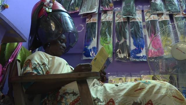as many african women spend much of their spare time in hair salons ivory coast's chief librarian also a woman has come up with a brainwave scheme to... - librarian stock videos & royalty-free footage