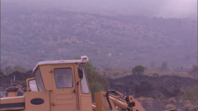 stockvideo's en b-roll-footage met as mount etna looms in the background, a bucket loader scoops up rocks and moves them. - handen in een kommetje