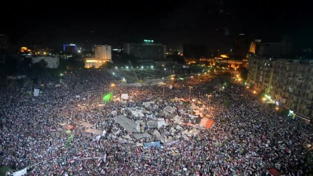 as night falls fireworks light up the sky above egypts tahrir square as hundreds of thousands of egyptians demonstrate against president mohammed... - army stock videos & royalty-free footage