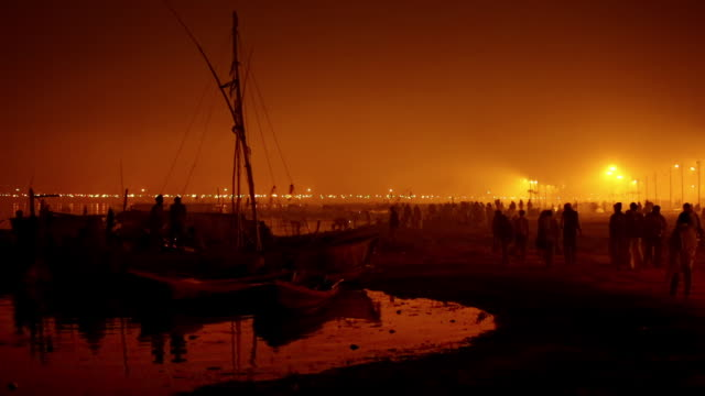 As night falls people walk to and fro along riverbank under brilliant flaring lights, while boatment settle in for the night. Kumbh Mela, India