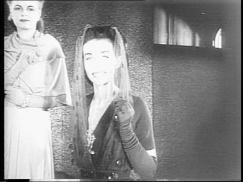 as part of the fashion show, a woman sketching a dress and pan up to model wearing white evening dress with dolphin silhouette / models in fur coats... - 1943 stock-videos und b-roll-filmmaterial