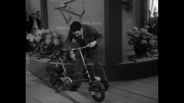 as people look on a couple mounts a small cart and drives away / couple in tiny car / man rides stops and folds up a small moped / man displays boot... - 1951 stock-videos und b-roll-filmmaterial