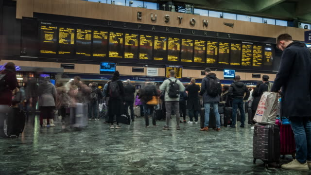 as people move rapidly through a station concourse other commuters stand looking towards a large digital arrivals and departure timetable at euston station london - commuter stock videos & royalty-free footage