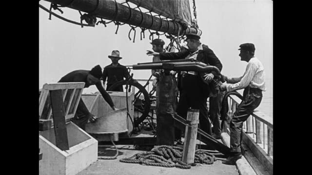 1923 as pirates attempt to shoot whale, unsure cabin boy (buster keaton) is pulled overboard when harpoon breaks - seeräuber stock-videos und b-roll-filmmaterial