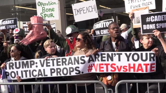 as president trump gives speech at veteran's day parade, anti trump protesters boo loudly and chant 'lock him up' carrying signs 'impeach' and 'cadet... - veterans day stock videos & royalty-free footage