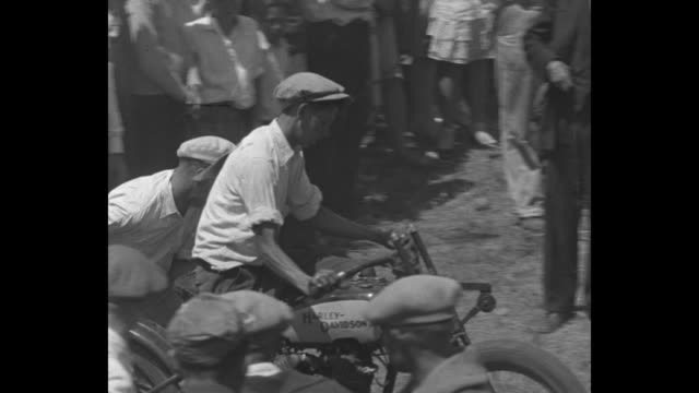 as scores of people watch, a motorcyclist attempts to climb a steep, dusty incline: the first man doesn't make it; at ground level, a guy starts the... - throttle stock videos & royalty-free footage