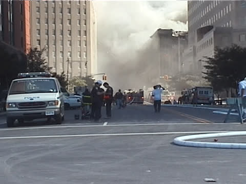 stockvideo's en b-roll-footage met as six world trade center burns in the background, nypd vehicles and trucks move into view, while a man carrying a large bottle of water walks down... - september 11 2001 attacks