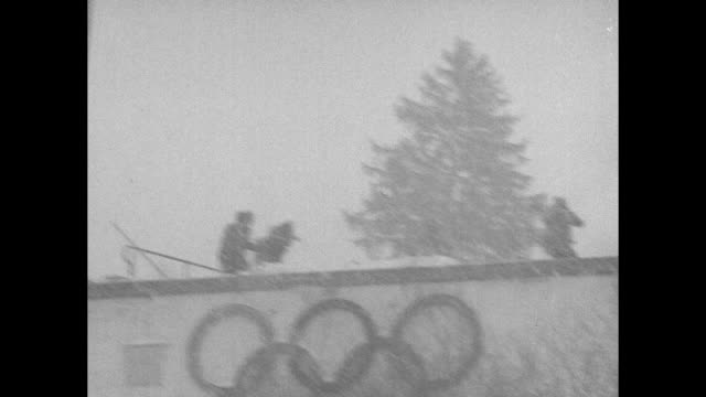 as snow falls skier comes down ski jump in olympic ski stadium in town of garmischpartenkirchen he goes off jump sails through air / vs skiers come... - garmisch partenkirchen stock videos & royalty-free footage