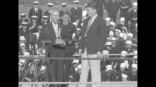 As sound men set up microphones in outdoor boxing ring Rep Frederick Britten and former heavyweight champ Gene Tunney climb into ring with sailors...