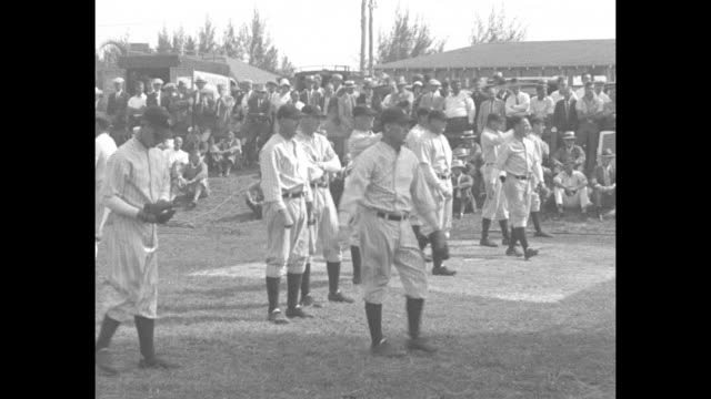 As spectators watch at rear the New York Yankees warm up during spring training in St Petersburg FL / VS Lou Gehrig bats runs / CU Yankee coach Jimmy...