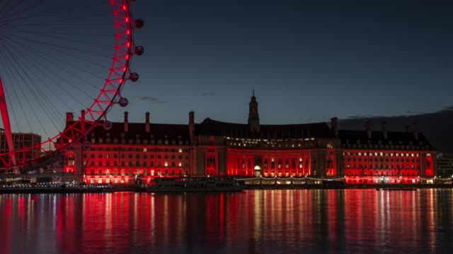 as the dawn light on the horizon grows colourful lights from county hall and the london eye reflect off the river thames - riverbank stock videos & royalty-free footage
