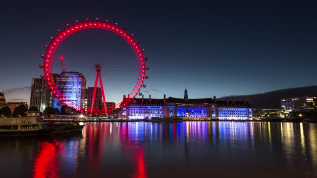 as the dawn light on the horizon grows colourful lights from the london eye and county hall are reflected off the river thames - millennium wheel stock videos & royalty-free footage