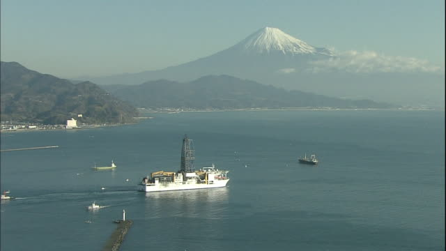 as the deep sea drilling vessel chikyu sails out of the port of shimizu mount fuji towers above suruga bay in the distance. - shizuoka prefecture stock videos and b-roll footage