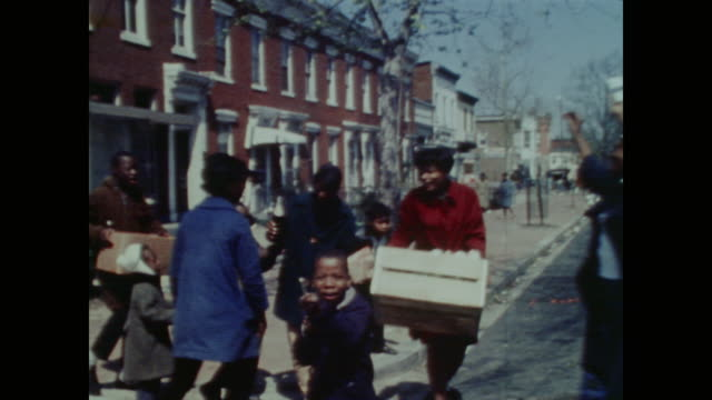 as the safeway grocery store burns, smiling looters young and old remove goods from the back of building - 1968 stock videos & royalty-free footage