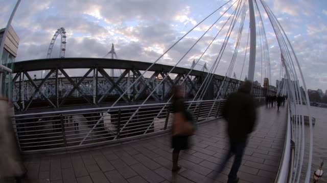 as the sun sets and evening approaches pedestrians use the queen's golden jubilee footbridge the cross over the river thames - london eye stock videos & royalty-free footage
