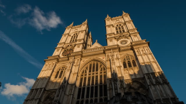 as the sun sets and evening arrives shadows travel up the facade of the great west door and tower of westminster abbey - westminster abbey stock videos & royalty-free footage