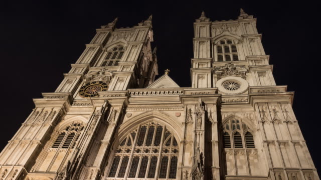 As the sun sets and evening arrives shadows travel up the facade of the Great West door and tower of Westminster Abbey