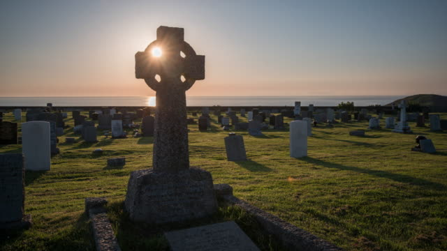 vidéos et rushes de as the sun sets over the irish sea it's light flares through a traditional celtic stone cross in a municipal cemetery as time passes grave stone shadows grow and night arrives - pierre tombale